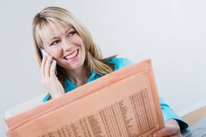 Woman Reading Stock Listings in Newspaper